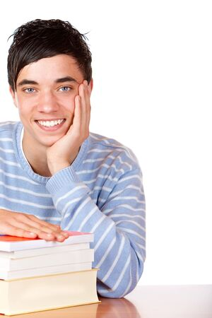 Young student is sitting on desk with his books and smiles happy into camera. Isolated on white. photo
