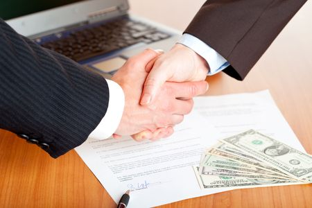 Handshake of businessmen with laptop, us dollar and contract in background.