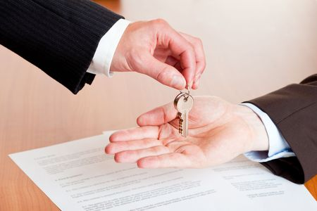 One businessman overgives a house or car key another businessmen. In background is a contract visible.