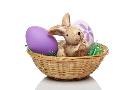 Closeup of easter bunny with egg in basket. Isolated on white. photo