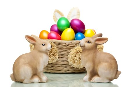 Two Easter bunnies sitting in front of basket full of colourful Easter  eggs. Isolated on white background. photo