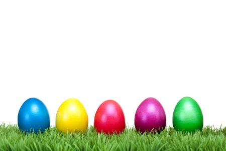 easter sunday: Several Colourful Easter eggs lying in a row on a green meadow. Isolated on white background. Stock Photo
