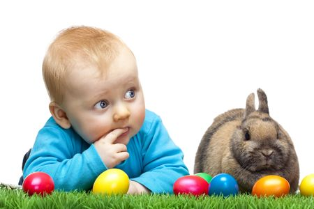 Cute young child is lying in meadow together with Easter bunny and colorful Easter eggs in meadow. Isolated on white Background. Stock Photo - 6632224