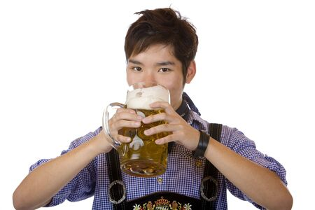 Asian man holding an Oktoberfest beer stein and drinks out of it. Isolated on white background. photo