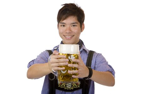 Asian man holding an Oktoberfest beer stein into camera and smiles happy. Isolated on white. photo