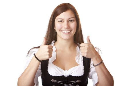 dirndl dress: Young beautiful woman with Oktoberfest Dirndl dress shows both thumbs. Isolated on white background. Stock Photo