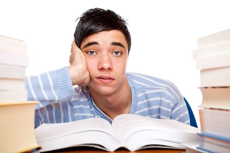 Young handsome student sitting on a desk between study books and looks frustrated. Isolated on white. Stock Photo