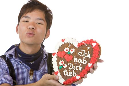 Chinese man, dressed with Bavarian Lederhose holds an Oktoberfest gingerbread heart in camera and gives a kiss. Isolated on white. photo