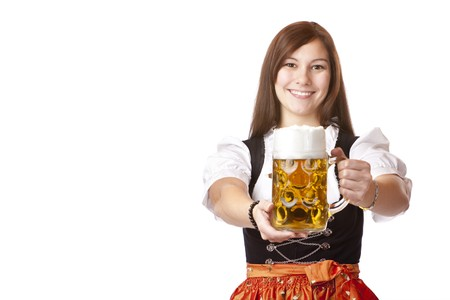 Young Bavarian woman holds Oktoberfest beer stein. Isolated on white background.