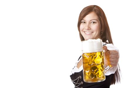 Smiling woman in Dirndl dress holds Oktoberfest beer stein (Mass). Cutout on white background.