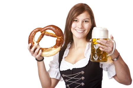 stein: Happy woman in dirndl dloth holding Oktoberfest beer stein and pretzel in hands. Isolated on white.