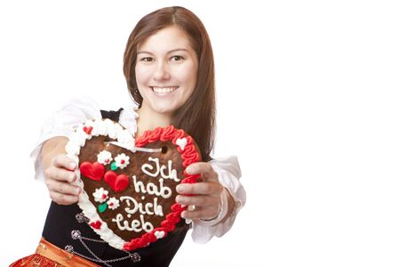 dirndl dress: Young happy smiling woman in dirndl dress holding Oktoberfest gingerbread heart. Isolated on white background.