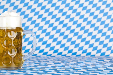 Oktoberfest beer stein  and Bavarian flag in background. Stock Photo - 7441696