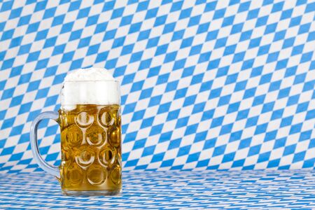 Oktoberfest beer stein  and Bavarian flag in background. Stock Photo - 7441672