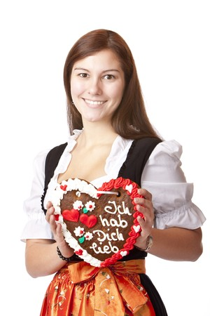 Woman in love dressed with Oktoberfest dirndl holding gingerbread heart. Isolated on white background. photo