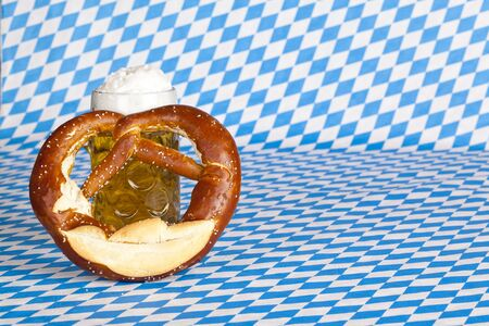 stein: Oktoberfest beer stein with pretzel and Bavarian flag in background. Stock Photo