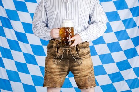 stein: Bavarian man with Oktoberfest beer stein (Mass) and leather pants (Lederhose). In background is Bavarian flag visible.