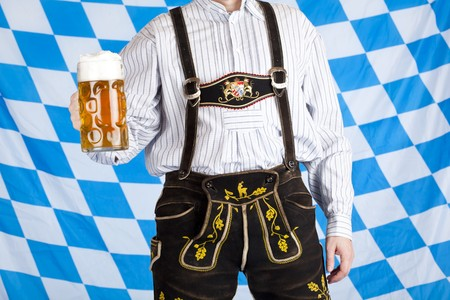 Bavarian man with Oktoberfest beer stein (Mass) and leather pants (Lederhose). In background is Bavarian flag visible.