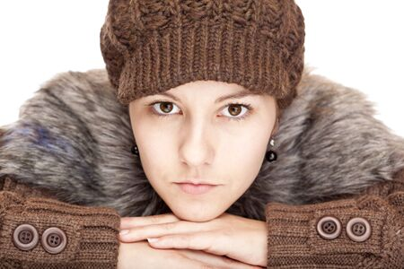 Beautiful young woman with pullover and cap looks serious. Isolated on white background. photo