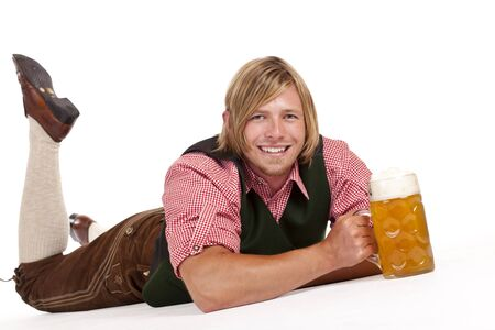 Happy man lying on floor holding oktoberfest beer stein. Isolated on white background. photo