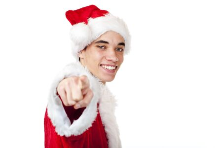 Smiling male teenager dressed as santa claus points with finger. Isolated on white background. photo