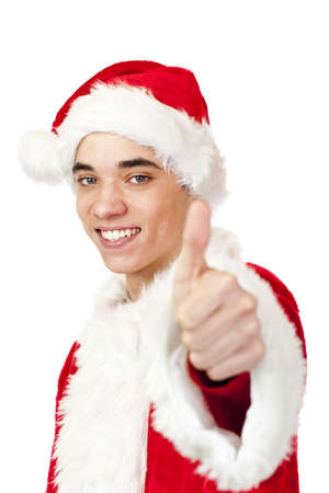 Smiling male santa claus teenager shows thumb up. Isolated on white background. photo