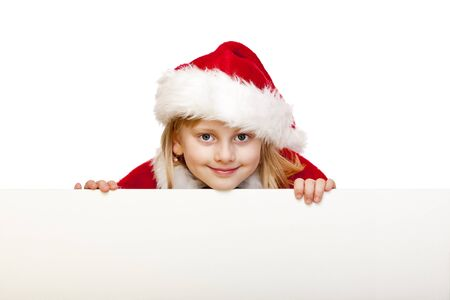 Small girl dressed as santa claus holds blank advertisement sign. Isolated on white background. photo