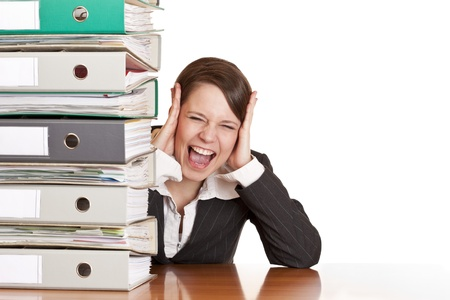 Frustrated business woman cries in office behind behind a folder stack. Isolated on white background. photo