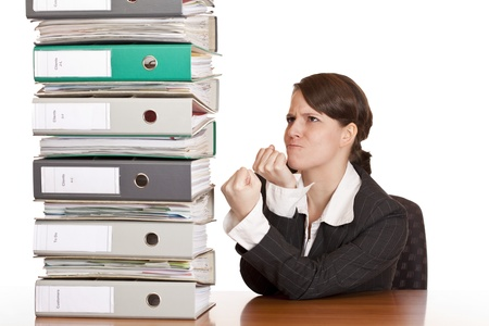 Business woman holds fists to file folder stack. Isolated on white background. photo