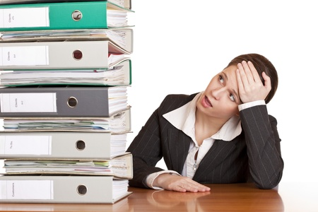 test deadline: Frustrated business woman in office looks at unbelievable folder stack. Isolated on white background. Stock Photo