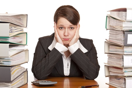 Frustrated overworked business woman in office between folder stack. Isolated on white background. photo