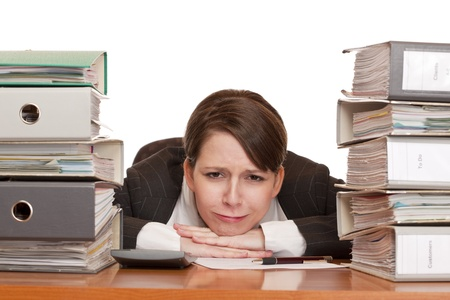 Woman in office with folder stacks is desperate, stressed and over-worked. photo