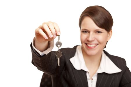key handover: Smiling woman gives over house key. Isolated on white background. Stock Photo