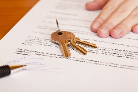 Handing over of keys after contract signing of house sale. Isolated on white background. Stock Photo