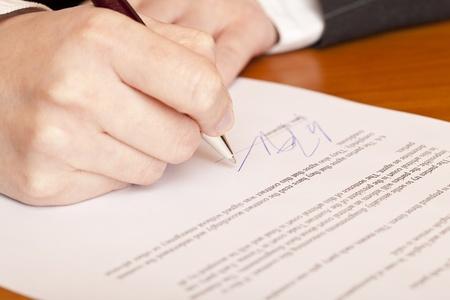 firmando: Primer plano macro de la firma de un contrato.