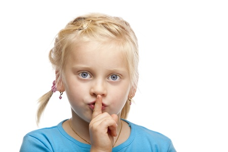 hist: Young blond girl holds finger on mouth. Isolated on white background. Stock Photo
