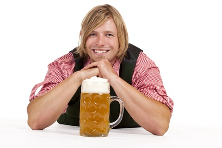 Man with lederhose and oktoberfest beer stein lying on floor. Isolated on white background. photo
