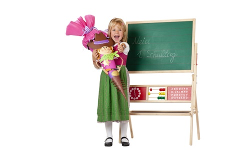 enquiring: Girl on first school day stands beside chalk board and shows thumb. Isolated on white background. Stock Photo