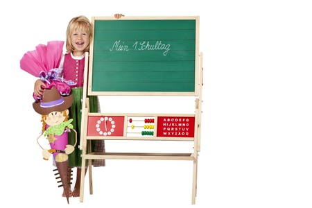 Girl on first school day stands beside chalk board. Isolated on white background. Stock Photo - 9079084