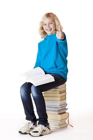 outwork: Feliz colegiala sentado en la escuela libros mostrando pulgar. Aislados sobre fondo blanco.