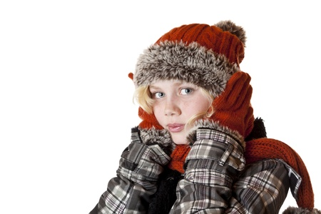shiver: Young blond girl in winter clothes warms her ears.Isolated on white background.