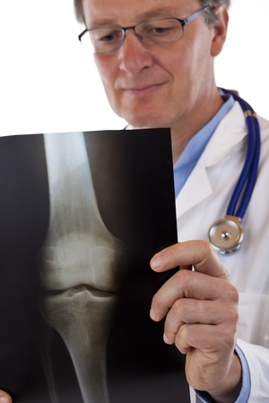 Elderly friendly doctor studies knee x-ray carefully. Isolated on white background.