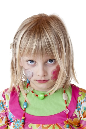 Blond disguised girl with painted cheeks looks serious.Isolated on white background. photo