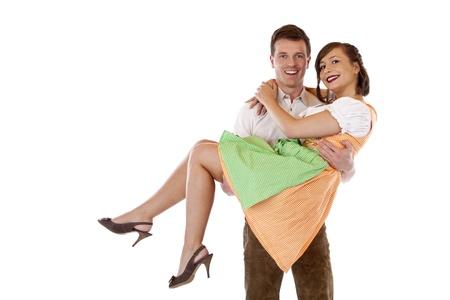 oneness: Bavarese man porta donna con camicetta sulle sue braccia e sorrisi. Isolato su sfondo bianco. Archivio Fotografico