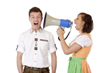 proclamation: Frustrated woman with Dirndl screams into ear of husband with megaphone. Isolated on white background.