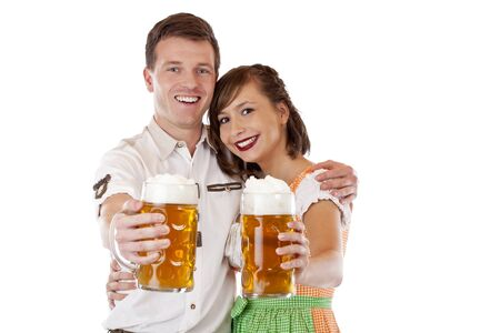 Young man and woman in dirndl holding oktoberfest beer stein. Isolated on white background. photo