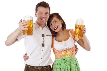 Bavarian man and woman in dirndl and lederhose with beer stein. Isolated on white background.