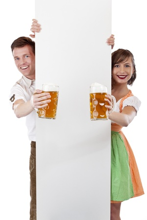 Young Bavarian man and girl in dirndl with adspace and beer stein. Isolated on white backgropund. photo