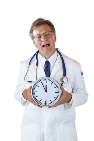 Stressed doctor with clock in front cries because of time pressure. Isolated on white background.