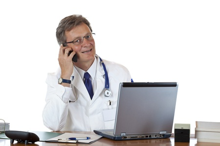 Friendly aged doctor sits at his desk and makes a phonecall.Isolated on white background. photo